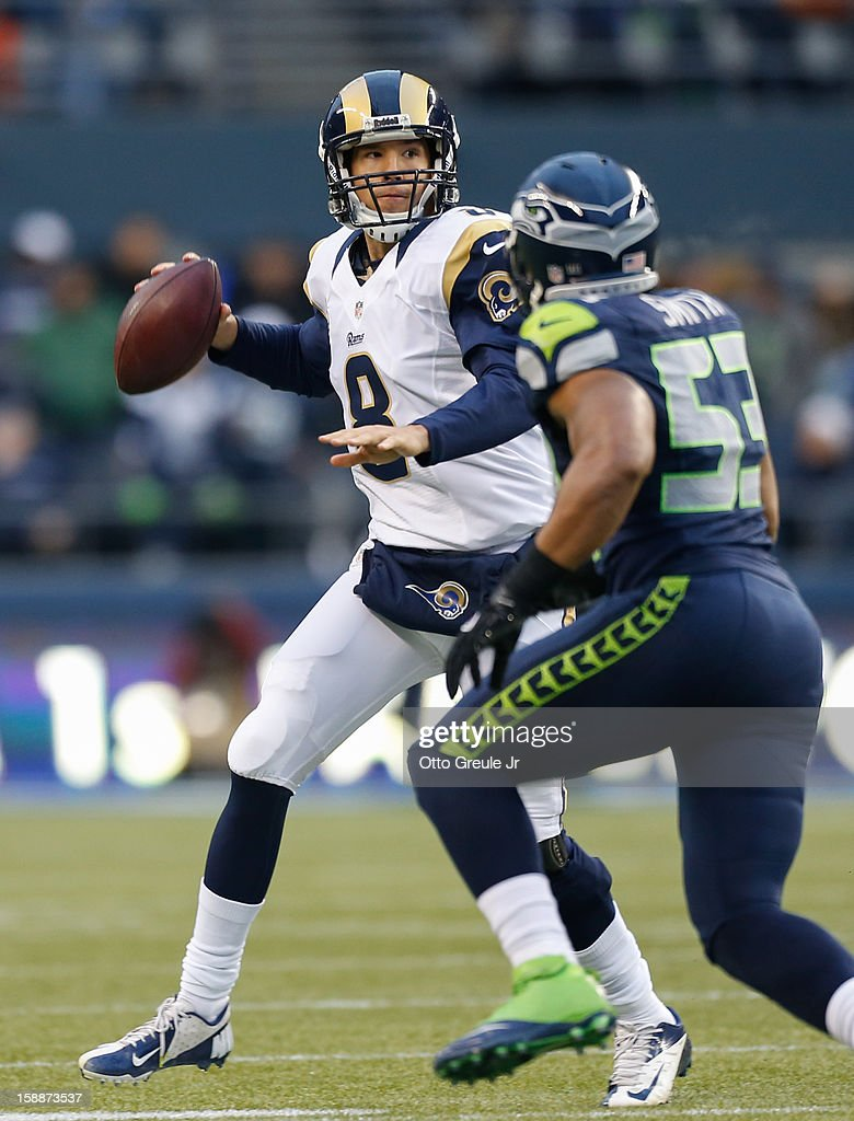 Quarterback Sam Bradford #8 of the St. Louis Rams passes against linebacker Malcolm Smith #53 of the Seattle Seahawks at CenturyLink Field on December 30, 2012 in Seattle, Washington.
