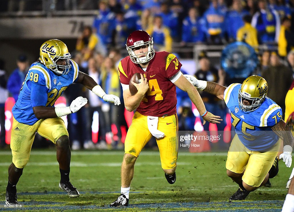 Quarterback Sam Darnold #14 of the USC Trojans eludes the rush from defensive lineman Takkarist McKinley #98 and defensive lineman Boss Tagaloa #75 of the UCLA Bruins during a 36-14 Trojan win at Rose Bowl on November 19, 2016 in Pasadena, California.