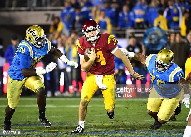 Quarterback Sam Darnold of the USC Trojans eludes the rush from defensive lineman Takkarist McKinley and defensive lineman Boss Tagaloa of the UCLA...