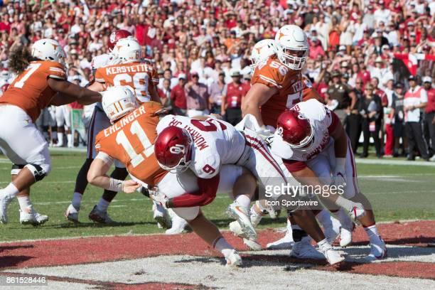 quarterback Sam Ehlinger of the Texas Longhorns is tackled by Sooners linebacker Kenneth Murray of the Oklahoma Sooners during the Oklahoma Sooners...