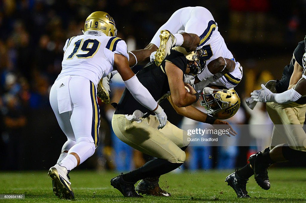 Quarterback Sefo Liufau #13 of the Colorado Buffaloes is hit by defensive back Tahaan Goodman #21 of the UCLA Bruins in the first quarter at Folsom Field on November 3, 2016 in Boulder, Colorado.