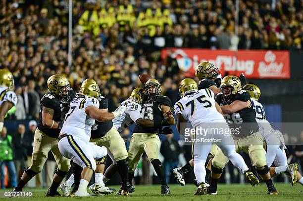 Quarterback Sefo Liufau of the Colorado Buffaloes is hit by defensive lineman Takkarist McKinley of the UCLA Bruins leading to a tipped pass and...