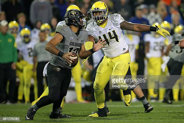 Quarterback Sefo Liufau of the Colorado Buffaloes tries to elude the rush of defensive lineman DeForest Buckner of the Oregon Ducks at Folsom Field...