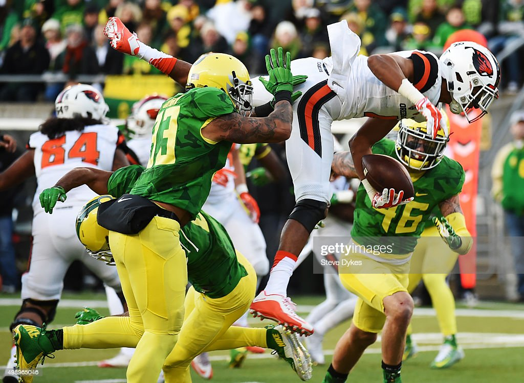 Quarterback Seth Collins of the Oregon State Beavers leaps over defensive back Charles Nelson of the Oregon Ducks for a touchdown during the third...