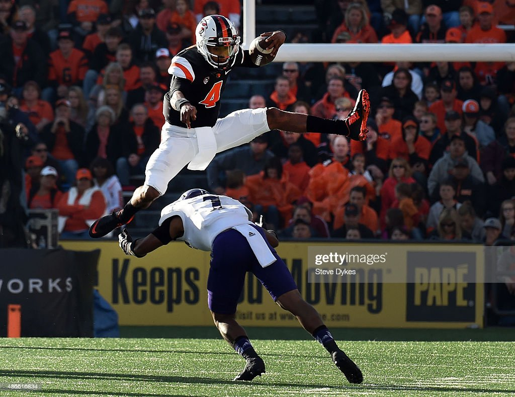 Quarterback Seth Collins of the Oregon State Beavers leaps over safety Josh Burton of the Weber State Wildcats diring the second quarter of the game...