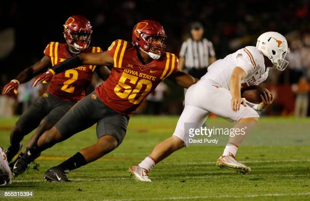 Quarterback Shane Buechele of the Texas Longhorns is tackled while scrambling for yards by defensive end Eyioma Uwazurike as linebacker Willie Harvey...