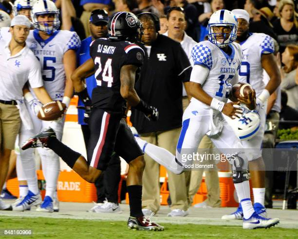 Quarterback Stephen Johnson of the Kentucky Wildcats sticks out his tongue at defensive back DJ Smith of the South Carolina Gamecocks as he runs out...
