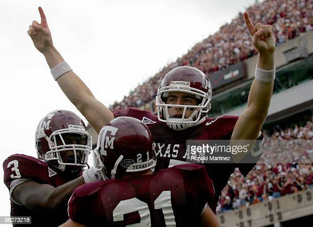 Quarterback Stephen McGee of the Texas AM Aggies celebrates his third quarter touchdown with Brandon Leone and Martellus Bennett during play against...