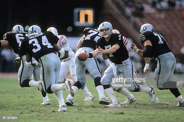 Quarterback Steve Beuerlein of the Los Angeles Raiders pitches to running back Bo Jackson during the game against the New England Patriots at the Los...