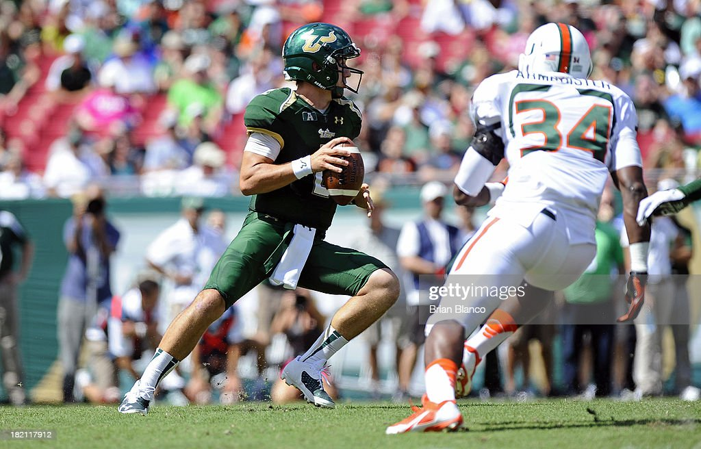 Quarterback Steven Bench #2 of the South Florida Bulls looks for an open receiver during the first quarter while getting pressure from linebacker Thurston Armbrister #34 of the Miami Hurricanes on September 28, 2013 at Raymond James Stadium in Tampa, Florida.
