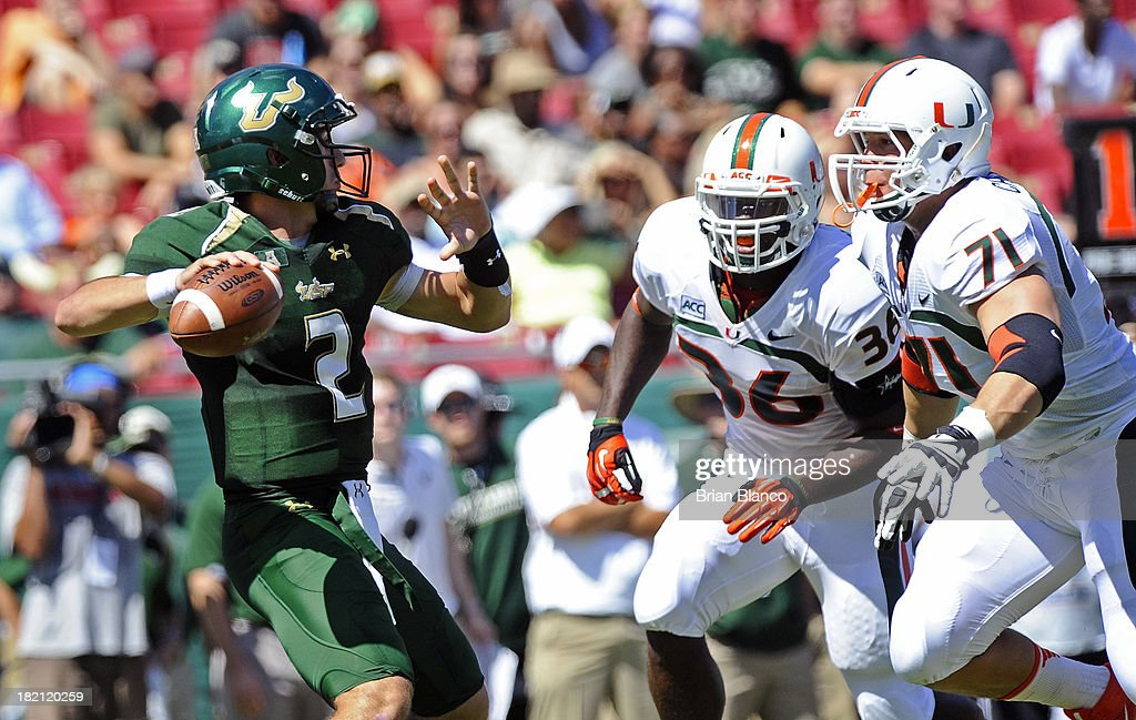 Quarterback Steven Bench #2 of the South Florida Bulls looks for an open receiver during the first quarter while getting pressure from linebacker Alex Figueroa #36 and defensive lineman Anthony Chickillo #71 of the Miami Hurricanes on September 28, 2013 at Raymond James Stadium in Tampa, Florida.