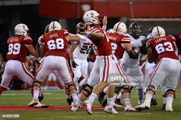 Quarterback Tanner Lee of the Nebraska Cornhuskers attempts a pass behind the offensive line against the Arkansas State Red Wolves at Memorial...