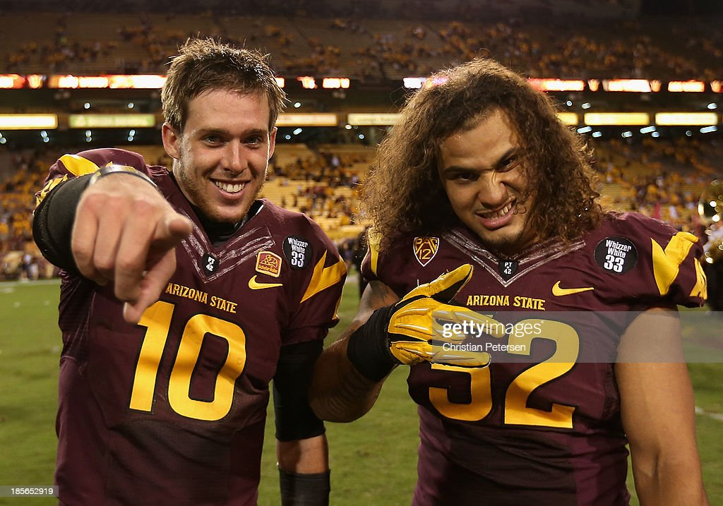 Quarterback Taylor Kelly #10 and linebacker Carl Bradford #52 of the Arizona State Sun Devils pose together following the college football game against the Washington Huskies at Sun Devil Stadium on October 19, 2013 in Tempe, Arizona. The Sun Devils defeated the Huskies 53-24.