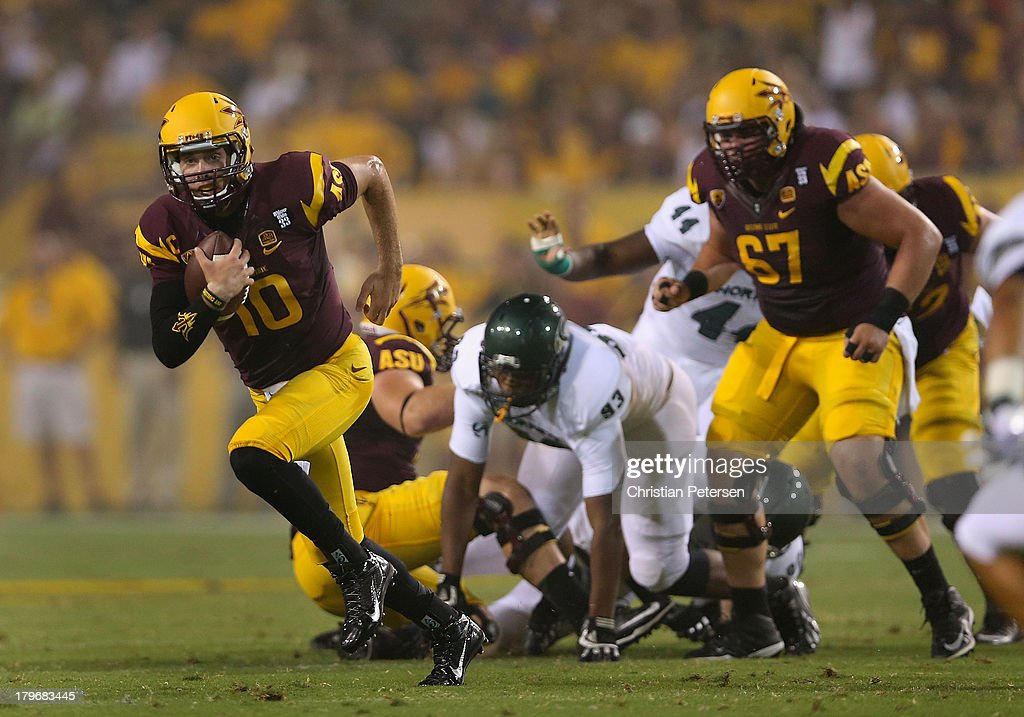 Quarterback Taylor Kelly #10 of the Arizona State Sun Devils scrambles with the football against the Sacramento State Hornets during the first quarter of the college football game at Sun Devil Stadium on September 5, 2013 in Tempe, Arizona.