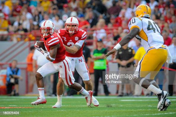 Quarterback Taylor Martinez of the Nebraska Cornhuskers hands the ball to running back Ameer Abdullah in front of linebacker CJ Perry of the Southern...