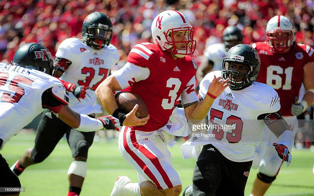 Quarterback <a gi-track='captionPersonalityLinkClicked' href=/galleries/search?phrase=Taylor+Martinez&family=editorial&specificpeople=7175179 ng-click='$event.stopPropagation()'>Taylor Martinez</a> #3 of the Nebraska Cornhuskers runs past linebacker Nick Nelms #53 and the Arkansas State Red Wolves' defense during their game at Memorial Stadium on September 15, 2012 in Lincoln, Nebraska. Nebraska won 42-13.