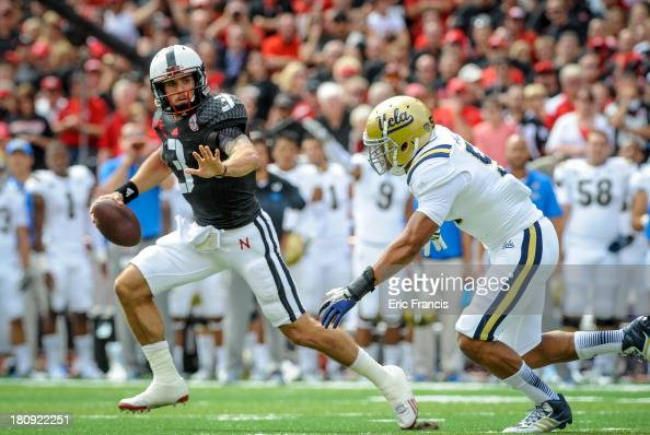 Quarterback Taylor Martinez of the Nebraska Cornhuskers runs past linebacker Aaron Wallace of the UCLA Bruins during their game at Memorial Stadium...