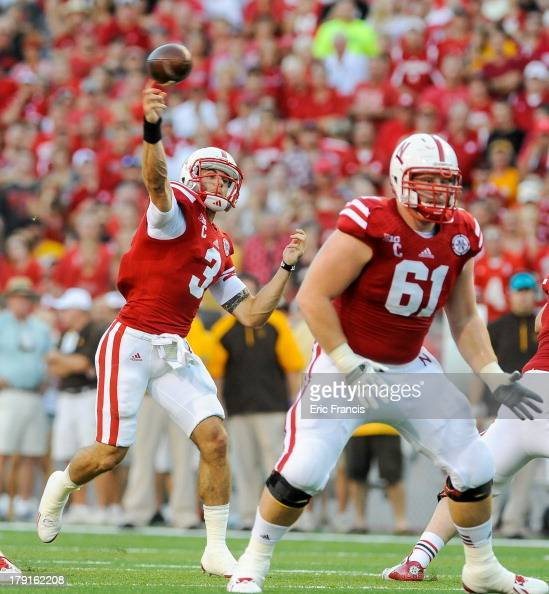 Quarterback Taylor Martinez of the Nebraska Cornhuskers throws over teammate offensive linesman Spencer Long and the Wyoming Cowboys during their...