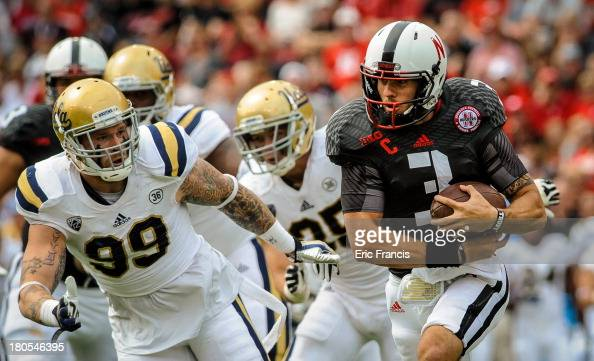 Quarterback Taylor Martinez of the Nebraska Cornhuskers tries to find a way around defensive end Cassius Marsh of the UCLA Bruins during their game...