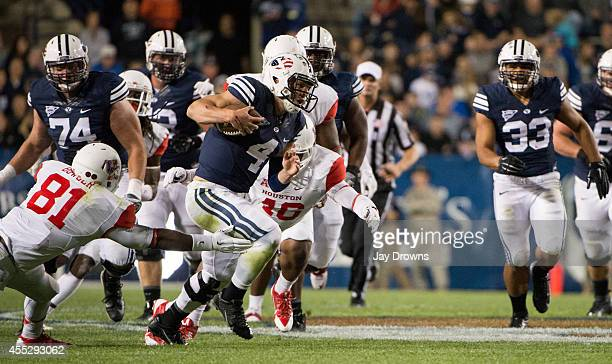 Quarterback Taysom Hill of the Brigham Young University Cougars eludes defensive end Tyus Bowser of the University of Houston Cougars on September 11...