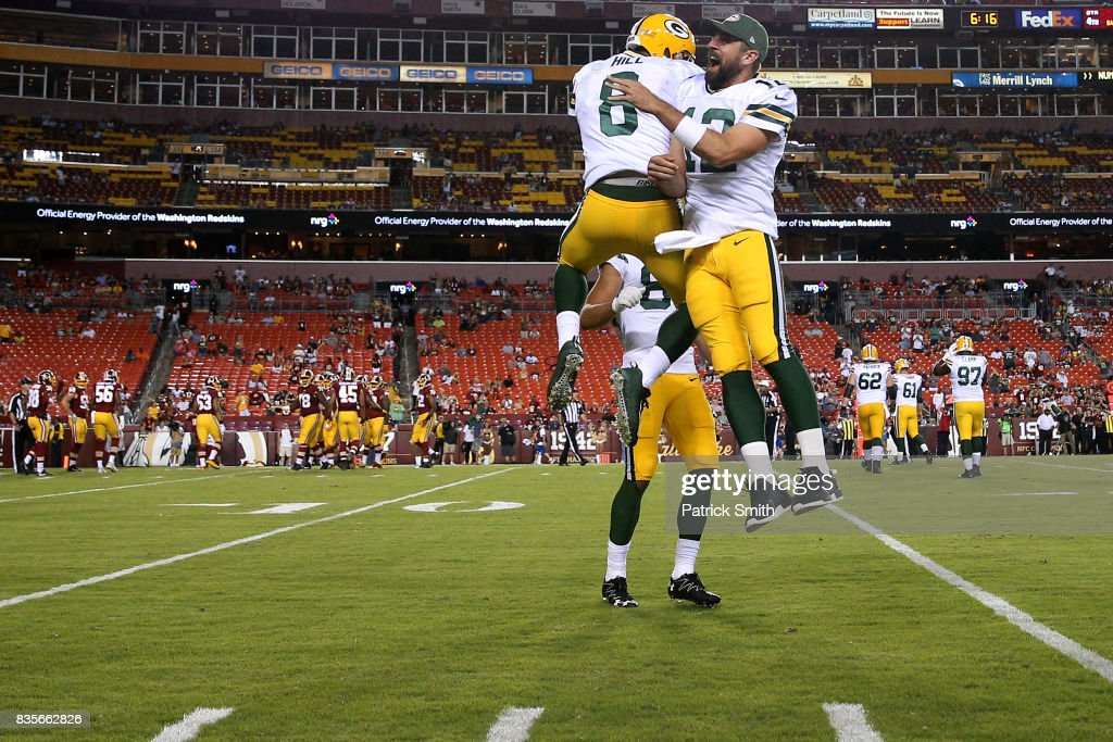 Quarterback Taysom Hill #8 of the Green Bay Packers celebrates after rushing for a touchdown with teammate Aaron Rodgers #12 against the Washington Redskins in the fourth quarter during a preseason game at FedExField on August 19, 2017 in Landover, Maryland.