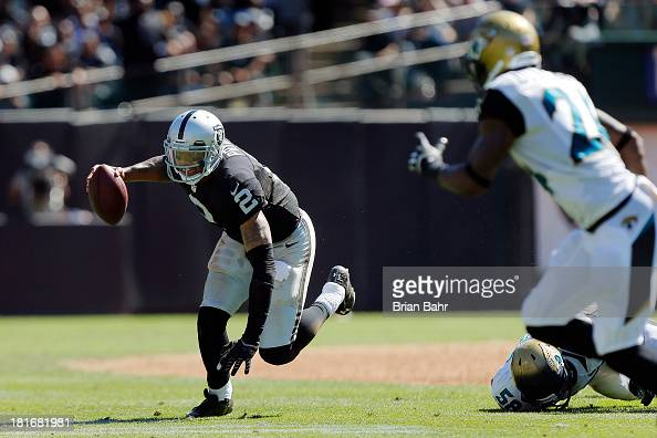 Quarterback Terrelle Pryor of the Oakland Raiders scrambles for 3 yards before getting tripped up by defensive end Jason Babin of the Jacksonville...