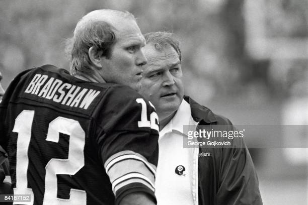 Quarterback Terry Bradshaw and head coach Chuck Noll of the Pittsburgh Steelers look on from the sideline during a game against the Cleveland Browns...