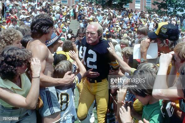 Quarterback Terry Bradshaw of the Pittsburgh Steelers walks through a group of fans as he goes to a practice field on media photo day at summer...