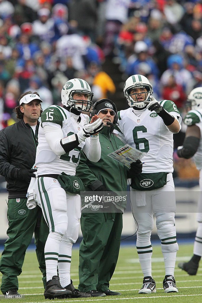 Quarterback Tim Tebow #15 and Quarterback Mark Sanchez #6 of the New York Jets follow the scoreboard with Offensive Coordinator Tony Sparano in the game against the Buffalo Bills when the Buffalo Bills host the New York Jets at Ralph Wilson Stadium on December 30, 2012 in Orchard Park, New York.