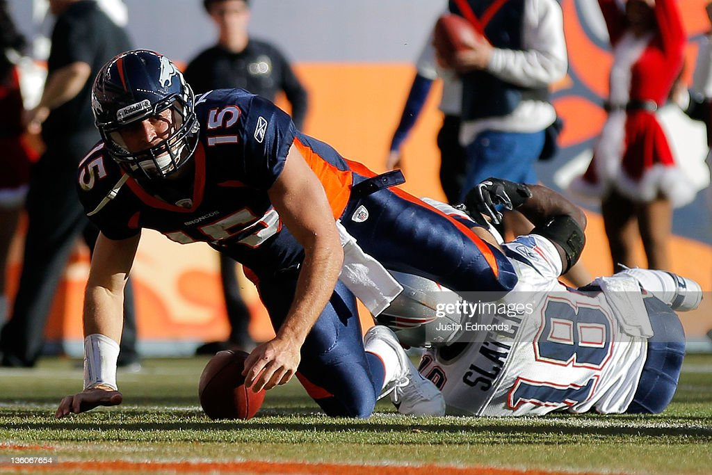 Quarterback <a gi-track='captionPersonalityLinkClicked' href=/galleries/search?phrase=Tim+Tebow&family=editorial&specificpeople=2729658 ng-click='$event.stopPropagation()'>Tim Tebow</a> #15 of the Denver Broncos scores a touchdown against the New England Patriots in the first quarter at Sports Authority Field at Mile High on December 18, 2011 in Denver, Colorado.