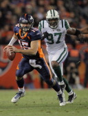Quarterback Tim Tebow of the Denver Broncos scrambles with the ball as Calvin Pace of the New York Jets pursues at Sports Authority Field at Mile...