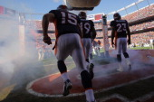 Quarterback Tim Tebow of the Denver Broncos takes the field along with teammates Eddie Royal and Willis McGahee to face the Pittsburgh Steelers at...