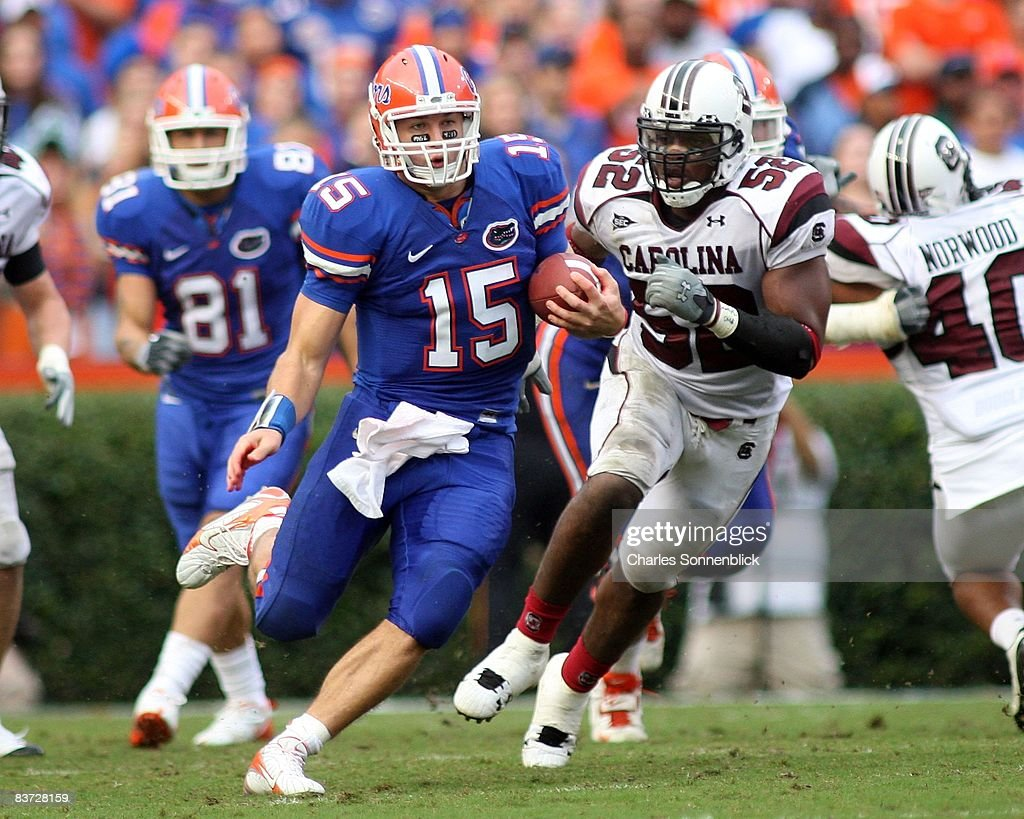 Quarterback Tim Tebow #15 of the Florida Gators breaks through the line while being chased by linebacker Jasper Brinkley #52 of the South Carolina Gamecocks during the game at Ben Hill Griffin Stadium on November 15, 2008 in Gainesville, Florida.
