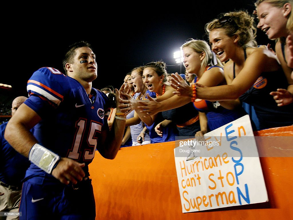 Quarterback Tim Tebow of the Florida Gators celebrates with fans after his team's victory over the Miami Hurricanes at Ben Hill Griffin Stadium on...
