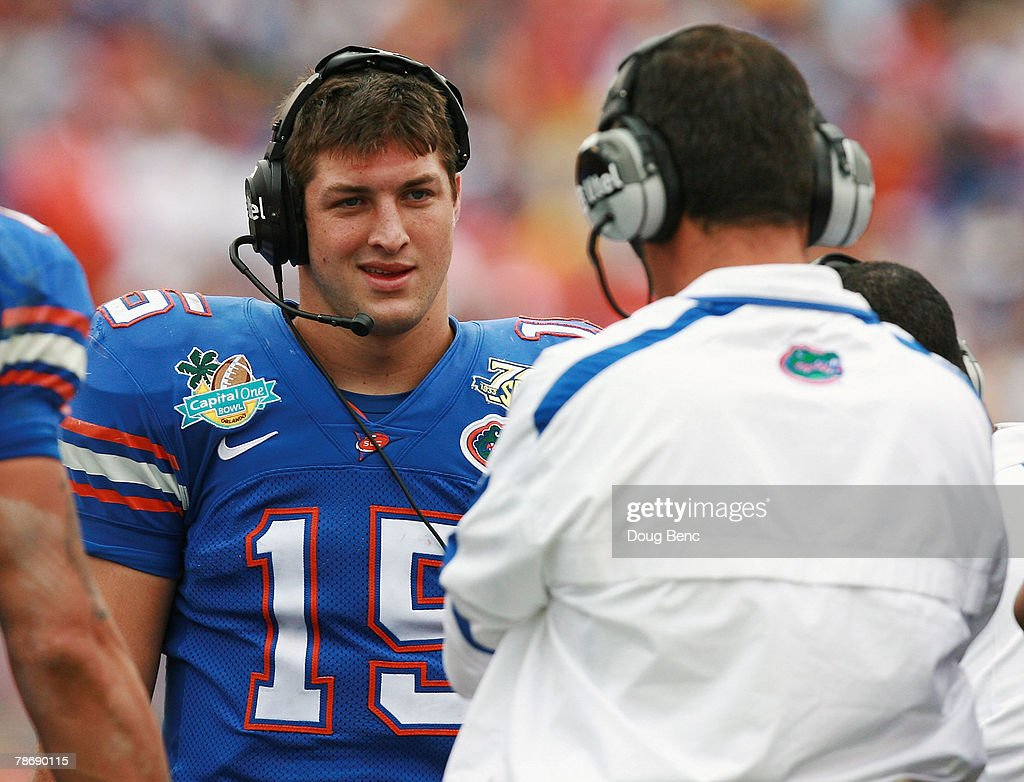 Quarterback Tim Tebow of the Florida Gators talks with head coach Urban Meyer during a stoppage in play while taking on the Michigan Wolverines in...