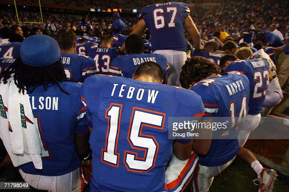 Quarterback Tim Tebow of the University of Florida Gators prays with teammates following the game against the Southern Miss Golden Eagles at Ben Hill...
