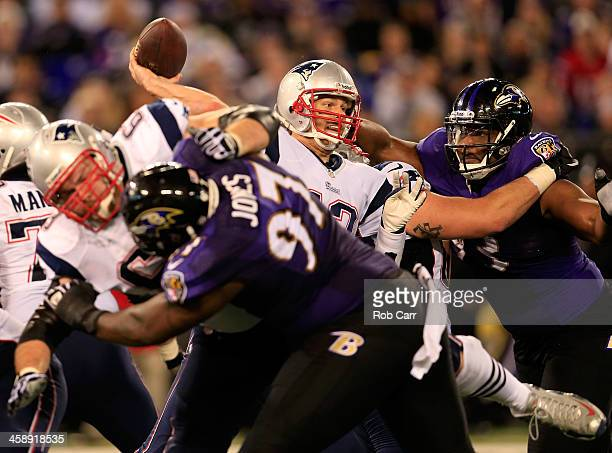Quarterback Tom Brady of the New England Patriots gets off a second half pass while being pressured by defensive end DeAngelo Tyson of the Baltimore...