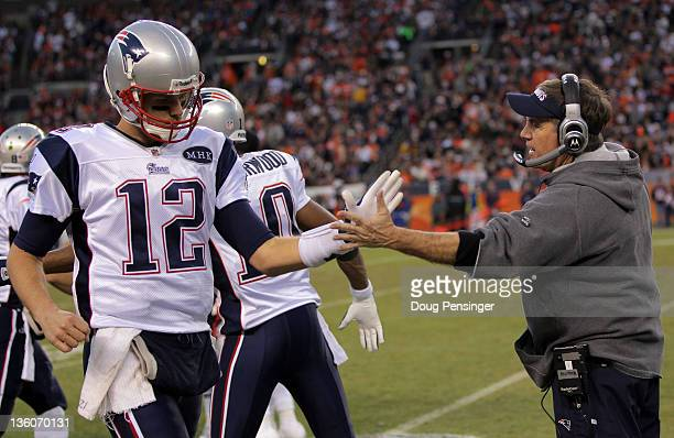 Quarterback Tom Brady of the New England Patriots highfives Head Coach Bill Belichick after scoring touchdown in the third quarter against the Denver...