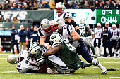 Quarterback Tom Brady of the New England Patriots is sacked by defensive end Sheldon Richardson and outside linebacker Calvin Pace of the New York...