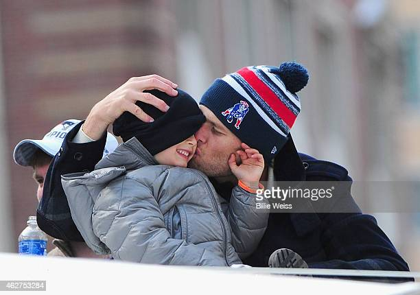 Quarterback Tom Brady of the New England Patriots kisses his son Benjamin during a Super Bowl victory parade on February 4 2015 in Boston...