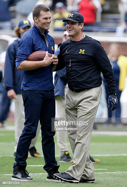 Quarterback Tom Brady of the New England Patriots laughs with head coach Jim Harbaugh of the Michigan Wolverines after they played catch before a...