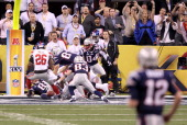 Quarterback Tom Brady of the New England Patriots looks down field as Antrel Rolle of the New York Giants and his teammates break up a hail mary pass...