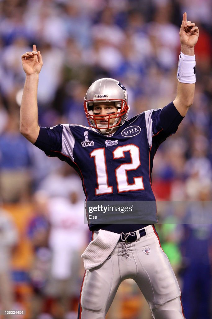 Quarterback <a gi-track='captionPersonalityLinkClicked' href=/galleries/search?phrase=Tom+Brady+-+Football+americano+-+Quarterback&family=editorial&specificpeople=201737 ng-click='$event.stopPropagation()'>Tom Brady</a> #12 of the New England Patriots reacts after throwing a 12 yard touchdown pass to Aaron Hernandez #81 against the New York Giants during Super Bowl XLVI at Lucas Oil Stadium on February 5, 2012 in Indianapolis, Indiana.