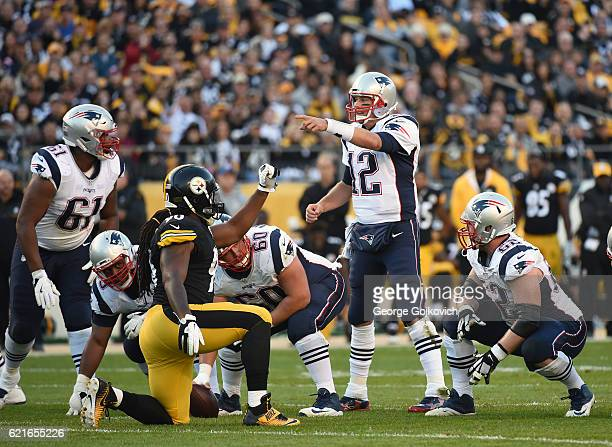 Quarterback Tom Brady of the New England Patriots signals at the line of scrimmage as defensive lineman Ricardo Mathews of the Pittsburgh Steelers...