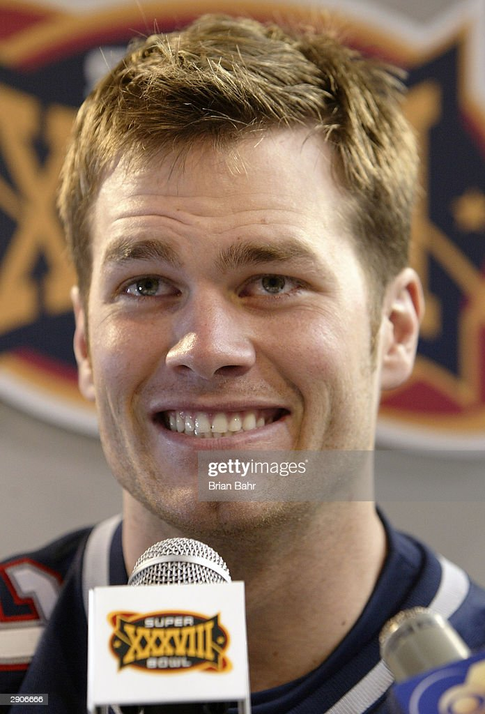 Quarterback <a gi-track='captionPersonalityLinkClicked' href=/galleries/search?phrase=Tom+Brady+-+American+Football+Quarterback&family=editorial&specificpeople=201737 ng-click='$event.stopPropagation()'>Tom Brady</a> #12 of the New England Patriots smiles as he answers questions on media day January 26, 2003 before Super Bowl XXXVIII against the Carolina Panthers in Houston, Texas.