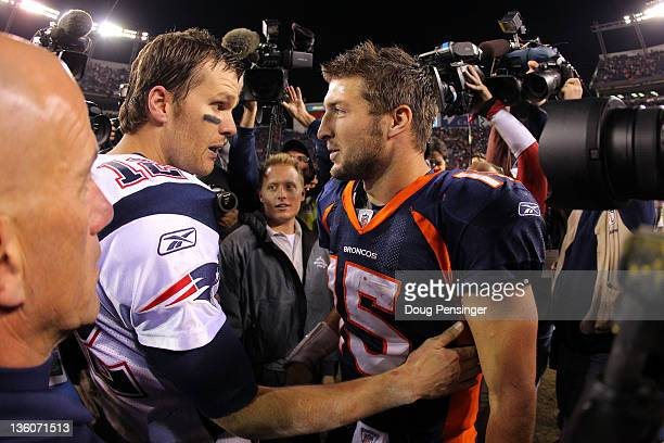 Quarterback Tom Brady of the New England Patriots talks with quarterback Tim Tebow of the Denver Broncos after the game at Sports Authority Field at...