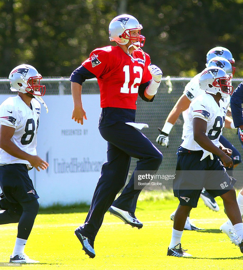 Quarterback Tom Brady runs and jumps during warmups at the start of practice. The New England Patriots held practice on the practice fields at Gillette Stadium.