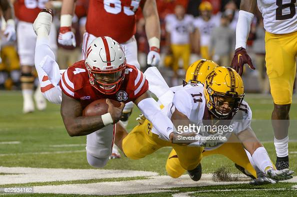 Quarterback Tommy Armstrong Jr #4 of the Nebraska Cornhuskers dives for extra yardage against defensive back Antoine Winfield Jr #11 of the Minnesota...