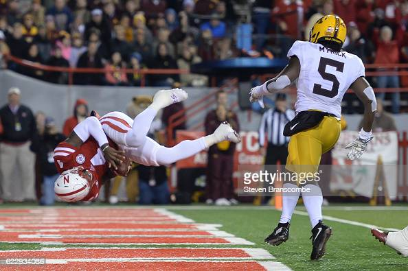 Quarterback Tommy Armstrong Jr #4 of the Nebraska Cornhuskers flips into the end zone to score against defensive back Jalen Myrick of the Minnesota...