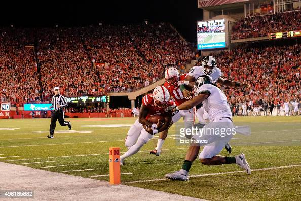 Quarterback Tommy Armstrong Jr #4 of the Nebraska Cornhuskers scores after he runs over defensive back Demetrious Cox of the Michigan State Spartans...